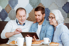 Positive man and their grandparents resting in the cafe. Its lunch time . Positive men using tablet with his grandparents and sitting in the cafe while spending Stock Images