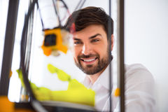 Positive man using 3d printer. Do it with pleasure. Cheerful delighted smiling man using 3d printer and expressing gladness royalty free stock photos