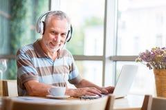 Positive man using laptop Stock Photo