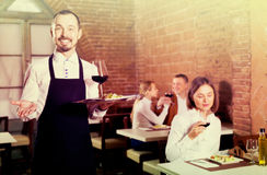 Positive man waiter demonstrating country restaurant. Positive men waiter demonstrating country restaurant to visitors Royalty Free Stock Image