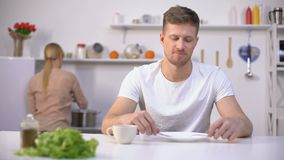 Positive man waiting for dinner, young wife cooking soup on background, hunger. Stock footage stock video