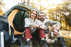 Positive man and woman drinking tea near tent Stock Image
