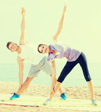 Positive man and woman training on beach by sea Stock Photography