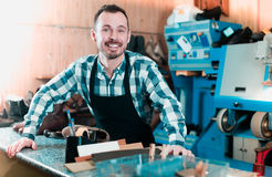 Positive man worker displaying his workplace. And tools in shoe repair workshop Royalty Free Stock Photo