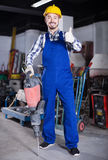 Positive man worker using jackhammer at workshop Royalty Free Stock Photos