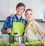Positive married couple cooking vegetable soup Stock Photo