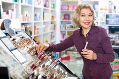 Positive mature blond woman choosing lip plumper on display Royalty Free Stock Photography
