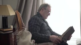 Positive mature caucasian old man sitting with photo album in front of window and smiling. Side view of senior retiree