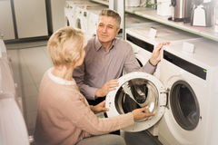 Positive mature couple chooses washing machine for their house i Stock Photography