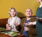 Positive mature couple having dinner at restaurant. Waiter serving an mature couple in a restaurant Royalty Free Stock Photography