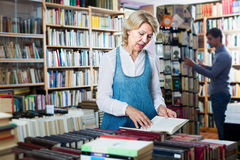 Positive mature female looking at open book in hands Royalty Free Stock Image