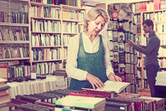 Positive mature female looking at open book in hands Royalty Free Stock Photos