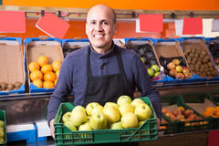 Positive mature male vendor in the grocery store. Positive mature male vendor selling apples in the grocery store Royalty Free Stock Photos