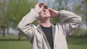 Positive mature man putting the cap on the head, protecting eyes from the sun rays and looking up in the park. Old man. Positive mature man putting the cap on stock footage