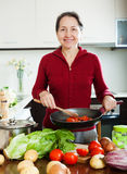 Positive mature woman cooking  with frying pan Royalty Free Stock Photos