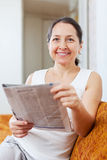 Positive mature woman with fresh newspaper Royalty Free Stock Images