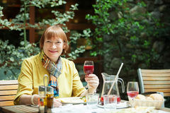 Positive mature woman  with  glass of wine Stock Image