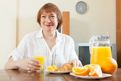 Positive mature woman having breakfast with croissants Stock Image