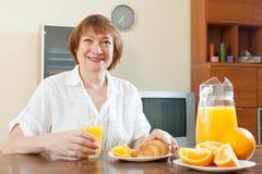 Positive mature woman having breakfast Royalty Free Stock Photos