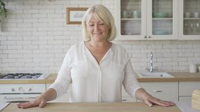 Positive mature woman looking at the camera smiling while standing in the modern kitchen. The senior woman going to stock video footage