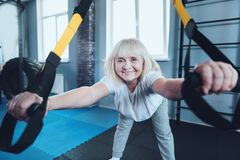 Positive mature woman smiling into camera while exercising at gym. Healthy retirement. Joyful elderly lady doing stretching exercise and using fitness rings Royalty Free Stock Image