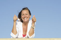 Positive mature woman thumbs up outdoor Stock Photo