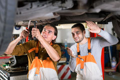 Positive mechanics repairing exhaust system Royalty Free Stock Photo