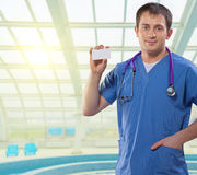 Positive medical doctor showing white vizit card standing on a b Royalty Free Stock Photography