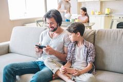 Positive man sits on sofa and plays on the phone. Boy has that phone as well but he looks at that his dad has. Girls are royalty free stock image