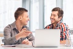 Positive men sitting at the table Stock Images