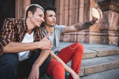 Cheerful males doing selfie on mobile outside royalty free stock photography