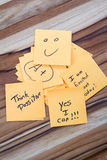 Positive messages on a desk. Close up of small sticky notes on a wooden desk , all with different positive notes Royalty Free Stock Image