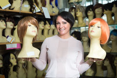 Positive middle aged female customer selecting natural hair wig Royalty Free Stock Images