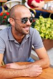 Positive middle-aged man. Alone behind table in summer cafe Stock Images