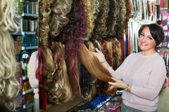 Positive  middle aged woman purchasing hair extension Royalty Free Stock Images