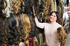 Positive middle aged woman purchasing hair extension stock photography