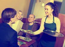 Positive middle class people enjoying food. Smiling middle class people enjoying food,happy waitress taking order. Focus on the waitress Stock Photo
