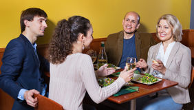 Positive  middle class people enjoying food and wine. Positive pleasant middle class people enjoying food and wine in cafe Royalty Free Stock Photos