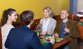 Positive  middle class people enjoying food and wine. Positive smiling happy middle class people enjoying food and wine in cafe Stock Image