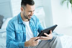 Cheerful guy using tablet computer and smiling. Positive mind. Joyful millennial gentleman grinning broadly while sitting on the edge of his bed and focusing his Stock Photo