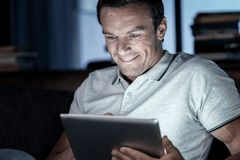 Positive minded man smiling while using tablet computer. Time to relax. Handsome adult gentleman wearing a polo shirt sitting on a sofa and smiling cheerfully Stock Photos