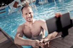 Positive minded millennial guy making selfies in swimming pool royalty free stock photos