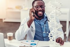 Positive minded young medical professional talking on phone and smiling Royalty Free Stock Photos