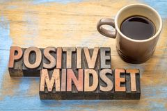 Positive mindset - word abstract in wood type. Positive mindset - word abstract in vintage letterpress printing blocks with a cup of coffee royalty free stock photo