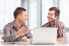 Positive Männer, die am Tisch sitzen Stockbilder