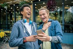Positive nice men looking at the funny picture. Positive mood. Nice positive men holding a smartphone while looking at the funny picture royalty free stock image