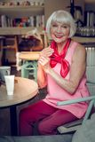 Positive cheerful woman sitting at the table stock photography