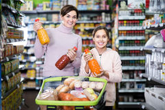 Positive mother with daughter choosing refreshing beverages in s. Positive mother with daughter choosing refreshing beverages on shelves in supermarket stock images