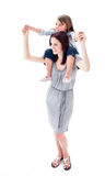 Positive mother giving her daughter piggyback ride Royalty Free Stock Photos