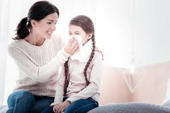 Positive mother helping her daughter with blowing her nose royalty free stock image